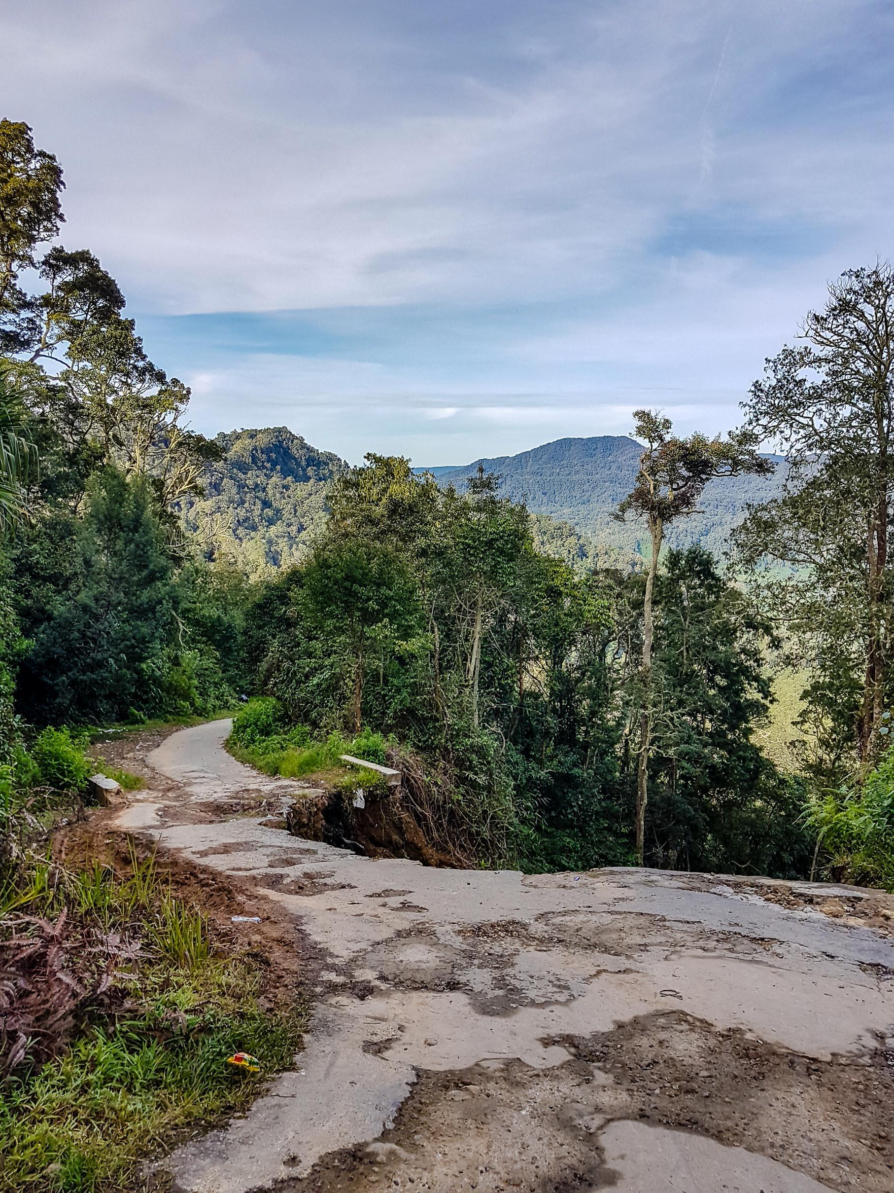 Droga asfaltowa z wyrwami prowadząca na Sibayak. Sibayak, Indonezja.
