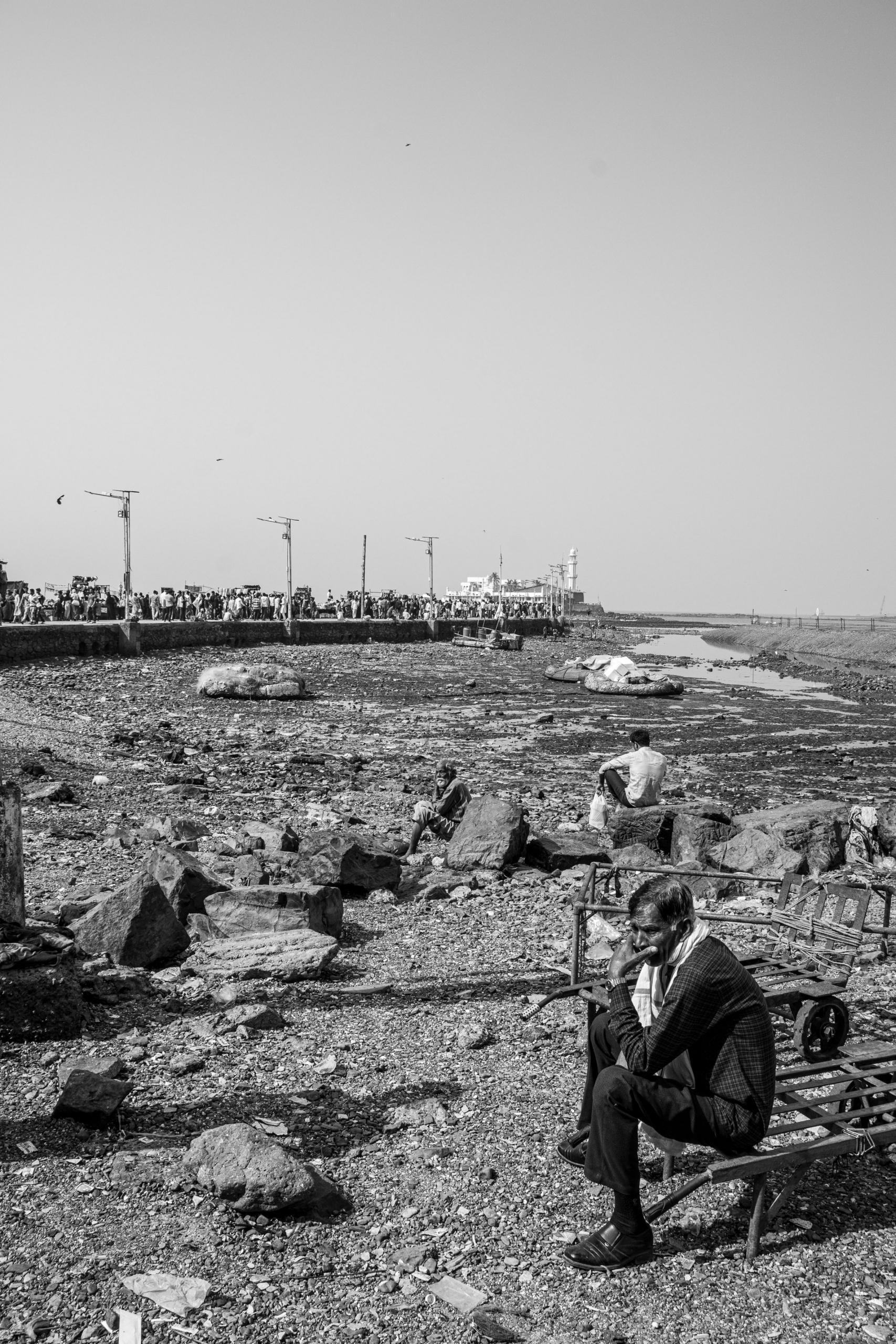 Znudzeni mężczyźni oczekują na nieoczekiwane. W tle grobla prowadząca do świątynii i meczetu. | Haji Ali Dargah | Mumbaj | Indie